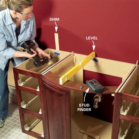 <b>Photo 13: Screw cabinet to the wall</b></br> Level the cabinets side-to-side and back-to-front using tapered shims and then screw them to the wall into the studs you located earlier. If your cabinet has a continuous panel along the entire back, cut away a portion to get at the plumbing. Use screw lengths that penetrate no more than 1 in. into the stud.