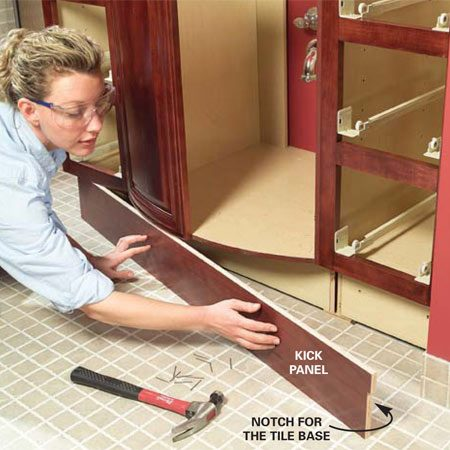 <b>Photo 14: Install the kick panel</b></br> Cut the kick panel to fit and then nail it to the cabinet. Notch the panel to fit around the base trim. Add spacers behind the kick panel if necessary to cover any flooring problems in front of the cabinets