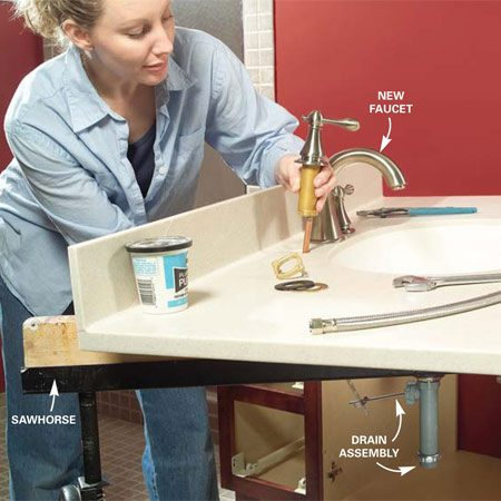 <b>Photo 17: Install the faucet and drain</b></br> Install the faucets and the drain assembly on the sink top before installing the top. Follow the directions that come with your new faucet and drain.