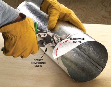 <b>Photo 1A: Right-handed offset snips in action</b></br> Cut a round duct from the right-hand side with green-handled compound snips. Use this technique if you're right-handed or in tight quarters. Keep the top blade aligned parallel to the cutting line to cut a straight line around the duct.