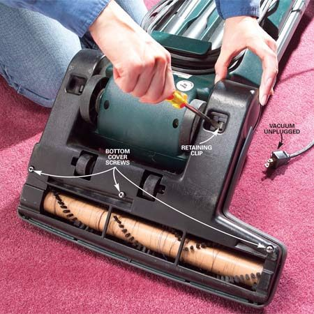 <b>Photo 1: Remove cover screws</b><br/>Unplug the vacuum and turn it over, exposing the underside. Back out the casing screws that secure the bottom cover. Release the attachment clips with a flat-blade screwdriver and lift off the cover.