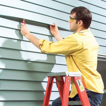 <b>Photo 1: Unlock siding using a zip tool</b></br> Slide the zip tool under the butt edge of the siding, hook the locking edge and pull down. Then slide the tool horizontally along the lock to release it. Lift the unlocked siding to expose the nailing hem of the siding piece below. Draw a line on the wall along the top of each siding course before you pull the nails.