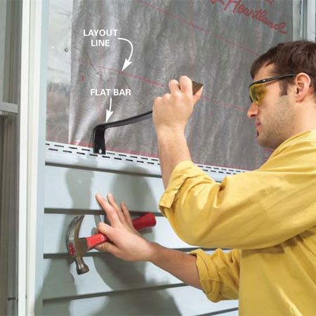 <b>Photo 2: Pull out the nails</b></br> Drive a flat bar between the nailheads and siding and carefully pull the nails. Then slide the piece down to unlock and remove it. Number each piece and set it aside. Remove siding until you expose enough wall to replace the window.