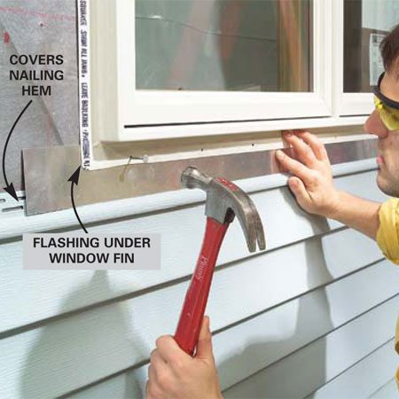 <b>Photo 3: Install the flashing under the window</b></br> Level and tack the new window in place, then cut a piece of aluminum flashing to width so it extends from the new window to overlap the nailing hem of the siding below. Slide the top edge under the window fin, then nail off the fin with roofing nails.