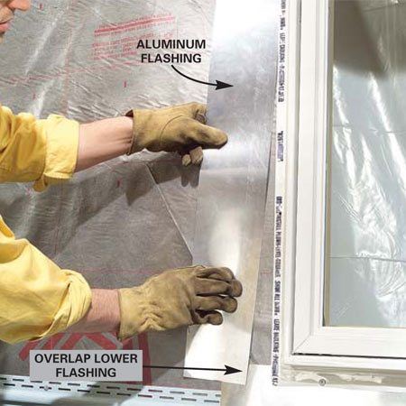 <b>Photo 4: Install flashing next to the window</b></br> Slide 5-in. wide side flashing under the window's nailing fin. Make sure it laps over the bottom flashing at least 2 in. and extends 2 in. above the window's top. Nail off the window.