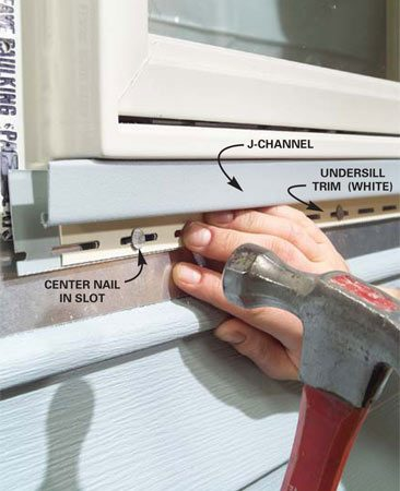 "<b>Photo 8: Install J-channel under the window</b></br> Position the J-channel under the window. Cut and position an undersill trim if necessary (see ""When to Use Undersill Trim.""). Drive roofing nails every 8 to 10 in. through the middle of the slots. Don't drive them tight. The trim pieces should slide back and forth slightly."