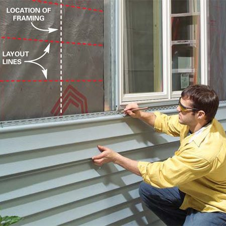 <b>Photo 11: Mark the cuts for siding under the window</b></br> Position the siding to be notched below the window. Mark it on each side of the window, allowing an extra 1/4-in. gap on each side for expansion. Measure from the locking tab of the siding below to the undersill trim to determine the depth of the notch.
