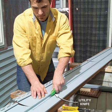<b>Photo 12: Cut the siding to fit under windows. </b></br> Cut through the nailing hem with shears, then score deeply along the rip line with a utility knife. Bend back the piece to snap off the notch.