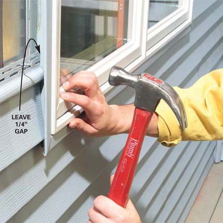 <b>Photo 13: Install the notched siding</b></br> Position the notched piece under the window, sliding it into the undersill trim and pushing the butt edge against the locking tab in the lower siding course to snap it in place. Make sure the top edge is on the layout line, then drive roofing nails at each stud.