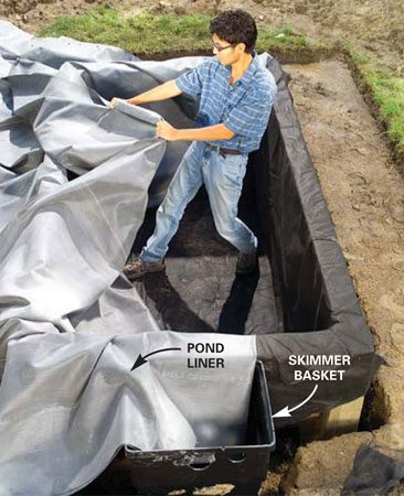 <b>Photo 8: Center the skimmer in the opening</b></br> Adjust the skimmer until it's centered over the opening and even with the top edge of the pond wall. Use gravel to elevate or level the skimmer basket as necessary. Hold it in place with a few shovelfuls of gravel around the bottom. Center the pond liner over the pond and tuck it into the inside bottom edges of the pond walls. Fold over the corners as neatly as possible.