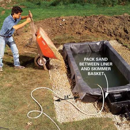 <b>Photo 10: Backfill the wall with gravel</b></br> Fill the pond with the garden hose, backfilling the pond walls with gravel at the same rate as the water fills the pond. Stop filling when the water flows into and fills the skimmer basket.