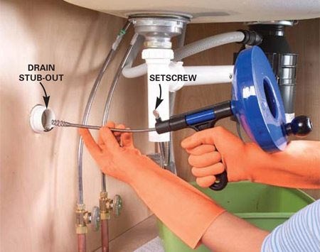 <b>Photo 6: Insert the snake</b></br> Thread the tip of the snake into the drain stub-out. Tighten the setscrew and turn the crank clockwise to feed it into the drainpipe.