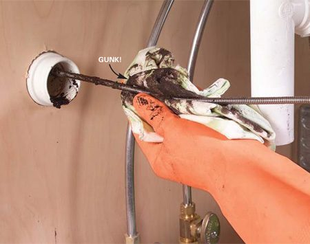 <b>Photo 8: Retract the snake</b></br> Pull the snake back out, cleaning the cable with a rag as you retrieve it. Reinstall the P-trap and run water to test the drain.