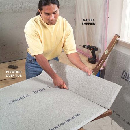<b>Photo 1: Cut the cement board</b><br/>Mark the tub wall lengths on the cement board and score one side with a utility knife. Snap at the line and cut the fiberglass mesh backing, just as you would with drywall. Smooth ragged edges with the knife or drywall rasp.