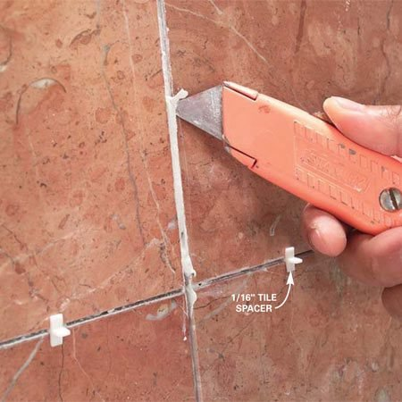 <b>Photo 7: Clean up excess mortar</b></br> Scrape excess mortar out of the joints before it hardens. If mortar oozes out above the tile surface, spread it a little thinner by flattening the angle of the trowel.