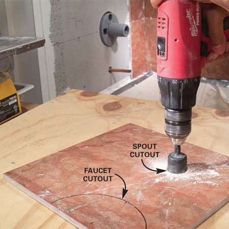 <b>Photo 9: Use a hole saw for small holes</b></br> Cut the hole for the tub and shower spouts with the 1-1/4 in. carbide-grit hole saw. Use light pressure to avoid cracking the tile.