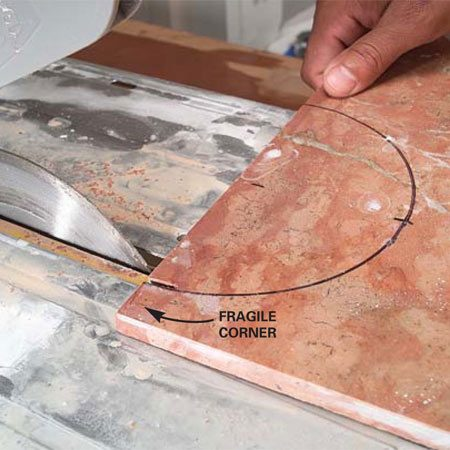 <b>Photo 10: Cut carefully near edges</b></br> Start cuts near narrow edges with the wet saw to avoid breaking the tile. Grind rough edges smooth if necessary with the saw blade.