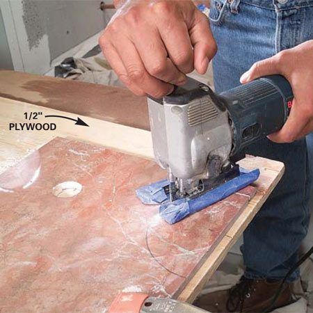 <b>Photo 11: Support the marble during cuts</b></br> Clamp the marble to 1/2-in. plywood to provide full support. Then cut through both with a carbide-grit blade. Cover the saw base with painter's tape to avoid scratching the tile.