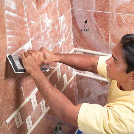 <b>Photo 13: Fill the joints with grout</b></br> Force grout into the joints with a rubber float, scraping diagonally across the tiles. Wipe off excess with a damp sponge. Polish off the light haze with a dry rag after the grout stiffens.