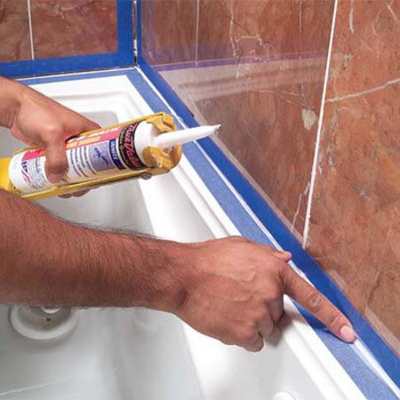 <b>Photo 14: Caulk the corners </b></br> Press tape along each side at all the corners. Squeeze caulk into the joints, smooth them, then immediately remove the tape.