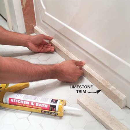 <b>Photo 15: Trim the edge of the tub </b><br/>Attach stone or tile trim to the front edge of the tub with silicone to cover an uneven floor/tub joint.
