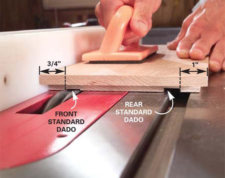 <b>Photo 7: Cut dadoes for the shelf standards</b></br> Lower the blade and cut 3/16-in. deep dadoes to receive the shelf standards in the side boards, holding the boards down firmly with the push pad.