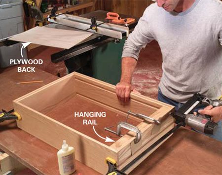 <b>Photo 8: Assemble the box</b></br> Apply glue to the rabbets, then clamp the box and nail the joints. Glue and nail on the hanging rail. Nail on the plywood back to square the box.