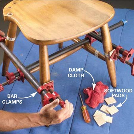<b>Photo 8: Clamp the legs and seat</b></br> Clamp the legs, rungs and seat all at once. Draw joints tight and wipe off glue drips with a damp cloth. Check its alignment on a flat surface.