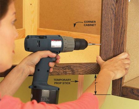 <b>Photo 1: Raise the cabinet</b></br> To raise a cabinet, remove the shelves and doors and then the screws securing it to the wall and cabinets on either side. Raise the cabinet, temporarily prop it in place, drill new pilot holes, then reinstall the screws.