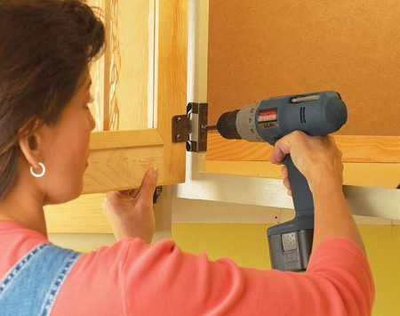 <b>Photo 1: Mount the new doors</b></br> Mount the hinges to the doors, then mount the doors to the face frames using the existing screw holes. Most hinges allow for some up-and-down movement and tilt so the doors can be adjusted evenly.