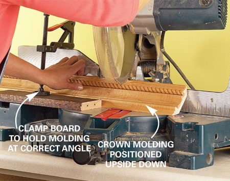 <b>Photo 2: Cut with a power miter saw</b></br> Cut the crown molding by placing it upside down and securing it at the correct angle with a clamp and wood scrap.