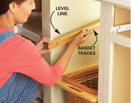 <b>Photo 2: Install the basket tracks</b></br> Cut the tracks to the proper width, then level them in both directions and screw them to the sides of the cabinet.