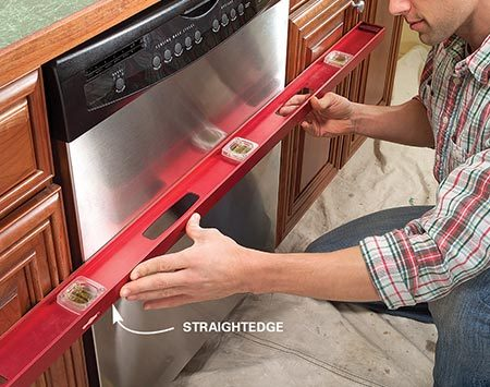 <b>Photo 9: Align the dishwasher</b></br> Slide the dishwasher back until it's flush to the cabinets. Positioning may vary slightly according to dishwasher styles and the style of your cabinets.