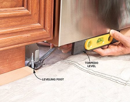<b>Photo 10: Level the dishwasher</b></br> Adjust the leveling feet with a wrench until the dishwasher is level (side to side) and plumb (up and down).