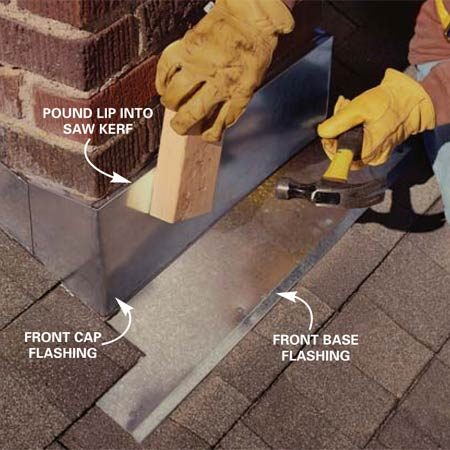 <b>Photo 9: Drive in the flange</b></br> Drive the flange on the cap flashing into the groove in the mortar joint. Use a block of wood to keep from denting the flashing.