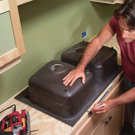 <b>Photo 4: Trace the sink and cut out the opening</b></br> Center the sink in the sink base cabinet and trace the perimeter. Draw another mark 1/2 in. inside this mark, radius the corners and cut it out with a jigsaw.