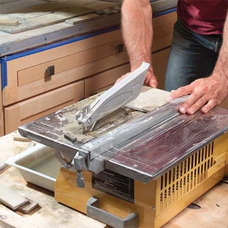 <b>Photo 11: Use a saw to cut the tiles</b></br> Cut the tiles to fit with a wet-cut tile saw. Push the tiles gently through the diamond blade; don't force them.
