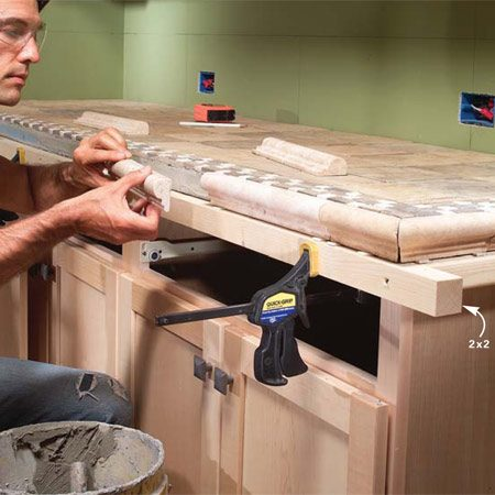 <b>Photo 13: Install the front edge</b></br> Clamp straight 2x2s to the front edge of the face frame to support the weight of the marble edge until the mortar sets. Set the edge pieces. Then draw layout lines on the backsplash and lay in tile according to your design.