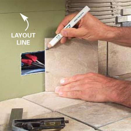 <b>Photo A: Mark the tile for height</b></br> Hold the backsplash tile in position and mark it for height to fit around the receptacle.