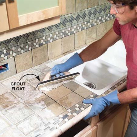 <b>Photo 15: Work the grout into the joints</b></br> Mix the grout to a toothpaste consistency and push it into the joints with a grout float. Mix enough for 6-ft. square sections and then wipe each section down as you go.
