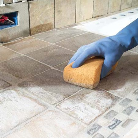 <b>Photo 16: Use a sponge to wipe away excess grout</b></br> Wipe the excess grout from the tile with a clean, wrung-out sponge. Several passes are necessary to clean the grout from the tile. Polish with a cotton towel.