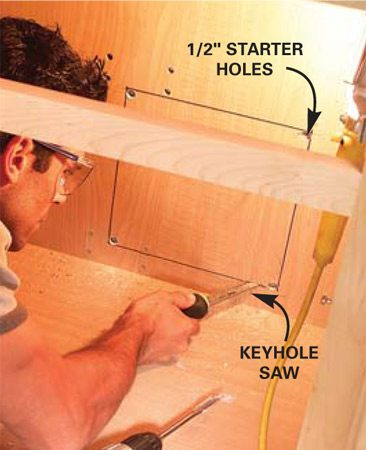<b>Photo 2: Open the wall</b></br> Drill starter holes and cut a 12-in. hole in the back of the cabinet to gain easy access to the outlet (power source). Keep the cut shallow to avoid nicking wires.