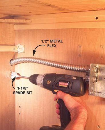 <b>Photo 4: Drill holes for horizontal runs</b></br> Drill 1-1/8 in. holes in the cabinet sides and feed flex from the metal junction box to each switch and light location.