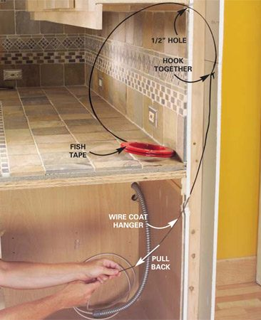 <b>Photo 8: Pull the wire up to the wall cabinet</b></br> Drill a 1/2-in. hole under the wall cabinet and push in the fish tape. Drill a 1-1/8 in. hole through the base cabinet and wall and push in a wire coat hanger to catch the fish tape. Pull the fish tape down, attach the cable and pull it up.