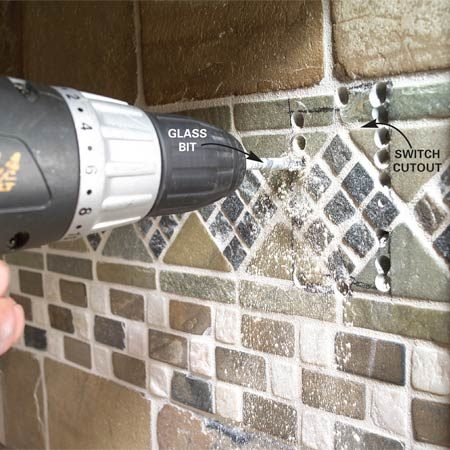 <b>Photo 11: Cut the hole for the switch</b></br> Mark the switch box profile on the backsplash. Drill a series of holes with a glass bit and chip out the tile and wallboard.