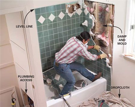 <b>Photo 4:  Remove the tub walls</b></br> Slice the drywall around the edge of the tile with a utility knife, then pry and break the old tile and drywall from the studs.