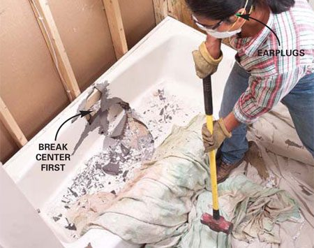 <b>Photo 5: Break the tub</b></br> Break cast iron tubs into manageable pieces with a sledge by covering a section with a drop cloth and then hitting that spot with sharp, controlled blows until it cracks. Wear safety gear.
