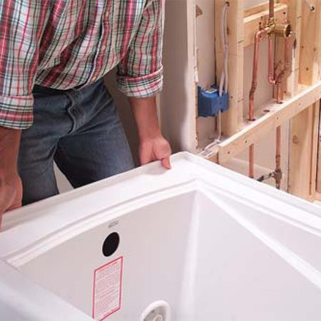 <b>Photo 11: Test-fit the tub</b></br> Lift the tub into place for a test fit. We had to remove additional drywall on both sides to get it in (Photo 12).
