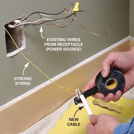 <b>Photo 6: Run a string through the receptacle opening. </b></br> Drop a weighted string down through the hole in the top plate and tape the end of the cable to it. Pull the cable up and route it over to the switch hole.