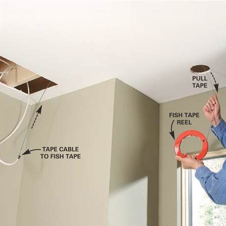 <b>Photo 7: Use a fish tape reel to pull cables through joist spaces. </b></br> To run cables through difficult areas, tape them to a metal fish tape and pull them back through joist spaces. o run cables through difficult areas, tape them to a metal fish tape and pull them back through joist spaces.